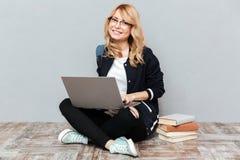 Estudiante de mujer joven sonriente que usa el ordenador portátil Fotos de archivo