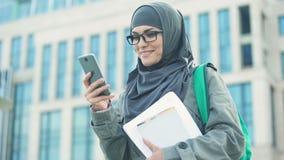 Estudiante de mujer musulmán feliz que charla en el teléfono al aire libre en campus universitario almacen de video