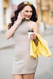 Estudiante de mujer que trabaja con un teléfono que sostiene un café y una chaqueta amarilla, llevando un vestido en la garganta, Fotos de archivo