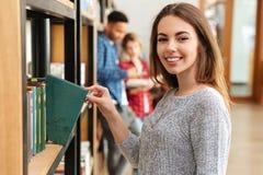 Estudiante de mujer sonriente joven que se coloca en libro de la biblioteconomía Imagenes de archivo
