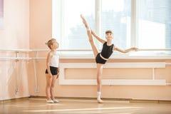Estudiante de observación del ballet de la muchacha más viejo que practica en la barra imagen de archivo libre de regalías