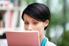 Estudiante de sexo femenino con el libro en la biblioteca foto de archivo