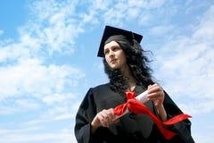 Estudiante de tercer ciclo feliz en capote con el diploma Fotos de archivo