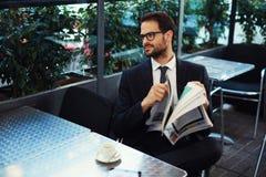 Estudiante de tercer ciclo que lee un anuncio de periódico sobre el café del trabajo y de la bebida Imagenes de archivo