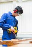 Estudiante de una clase de la carpintería que perfora un agujero Fotografía de archivo