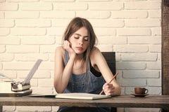 Estudiante del adolescente en delantal de la mezclilla en la pared de ladrillo blanca Foto de archivo libre de regalías