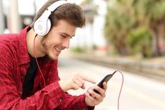 Estudiante del adolescente que aprende con curso en línea en un teléfono elegante Imagenes de archivo