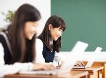 Estudiante del adolescente que aprende en línea con el ordenador portátil en sala de clase imagen de archivo libre de regalías