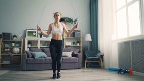 Estudiante del ajuste que hace los deportes en casa que saltan la cuerda en la elaboración de la sala de estar metrajes