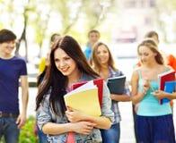 Estudiante del grupo con el cuaderno en el banco al aire libre. Fotografía de archivo