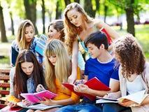 Estudiante del grupo con el cuaderno en el banco al aire libre. Imagen de archivo libre de regalías