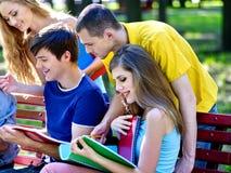Estudiante del grupo con el cuaderno en el banco al aire libre Imagen de archivo
