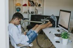 Estudiante del hombre joven en la mesa con el teléfono móvil Imagenes de archivo