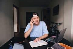 Estudiante del hombre joven que habla en el teléfono que se sienta en el escritorio en el cuarto Enseñanza en casa Imagenes de archivo