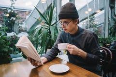 Estudiante del inconformista en casquillo y camisa que lee un libro y que bebe el café en un café con el invernadero Imagen de archivo libre de regalías