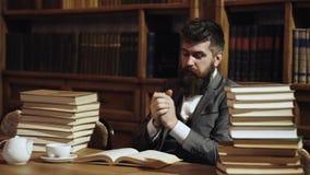 Estudiante del inconformista que estudia en biblioteca Investigación y concepto el estudiar Hombre en traje clásico, profesor con metrajes