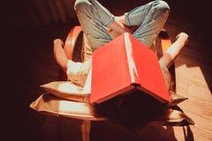 Estudiante del inconformista que toma una siesta en silla moderna cómoda con el libro de papel en la cabeza Luz natural Día asole Foto de archivo libre de regalías
