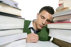 Estudiante del muchacho que duerme sobre los libros de la pila sobre el escritorio Fotografía de archivo libre de regalías