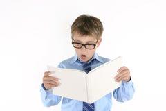 Estudiante del niño que lee un libro imagenes de archivo