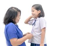 Estudiante del uniforme de preparación de la madre su hija imagen de archivo