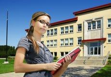 Estudiante delante de la entrada de la escuela Imagen de archivo libre de regalías