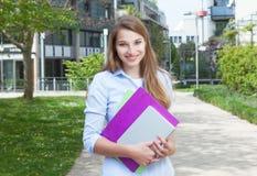 Estudiante derecho con el pelo rubio largo en campus Imagenes de archivo