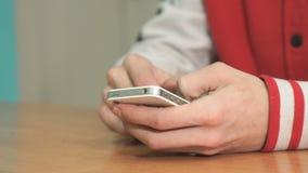 Estudiante desconocido que sostiene el smartphone plata-blanco almacen de metraje de vídeo