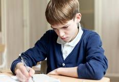Estudiante diligente que se sienta en el escritorio, sala de clase Fotografía de archivo libre de regalías