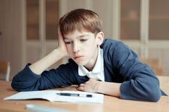 Estudiante diligente que se sienta en el escritorio, sala de clase imagen de archivo libre de regalías