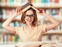 Estudiante divertida cansada con los libros de lectura de los vidrios Foto de archivo libre de regalías