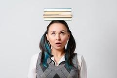Estudiante divertida con una pila de libros en su cabeza fotos de archivo libres de regalías