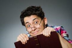 Estudiante divertido con muchos libros Imagen de archivo libre de regalías
