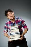 Estudiante divertido con muchos libros Imagenes de archivo