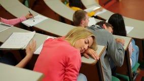 Estudiante dormido en el escritorio en sala de conferencias metrajes