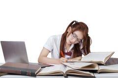 Estudiante dulce con los vidrios que estudia en el escritorio Imagenes de archivo