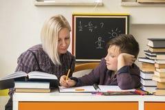 Estudiante durante la preparación con la ayuda de un profesor particular ayuda Imagen de archivo
