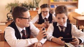 Estudiante durante una lección, jugando en un smartphone, ocultando del profesor almacen de metraje de vídeo