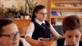 Estudiante durante una lección, jugando en un smartphone, ocultando del profesor almacen de video