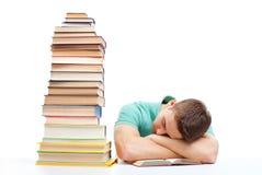 Estudiante durmiente que se sienta en el escritorio con la alta pila de libros Imagenes de archivo