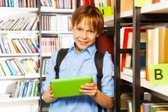 Estudiante elemental con la tableta en biblioteca Imagen de archivo libre de regalías