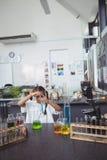 Estudiante elemental que hace el experimento con la sustancia química azul en el laboratorio Imágenes de archivo libres de regalías