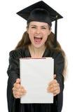 Estudiante emocionada de la graduación que muestra el libro Fotografía de archivo libre de regalías