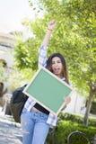 Estudiante emocionado Holding Blank Chalkboard de la raza mixta fotografía de archivo