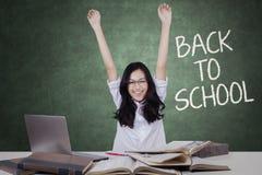 Estudiante emocionado que aumenta las manos en sala de clase Imagen de archivo libre de regalías