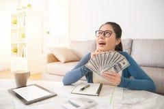 Estudiante emocionado que lleva a cabo el dólar del dinero Imagenes de archivo