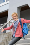 Estudiante emocionado que resbala abajo de la verja en la escalera Fotografía de archivo libre de regalías