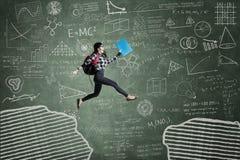 Estudiante emocionado que salta en hueco Imagen de archivo libre de regalías