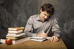 Estudiante emocional con los libros y manzana roja en sitio de clase, en la pizarra Foto de archivo