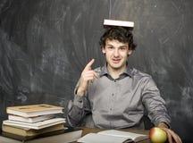 Estudiante emocional con los libros y manzana roja en sitio de clase, en la pizarra Fotografía de archivo