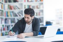 Estudiante en biblioteca escolar usando el ordenador portátil para la investigación Imagen de archivo